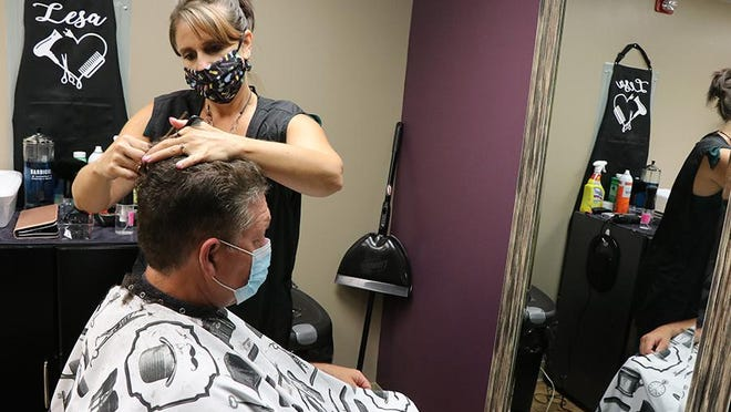 Lesa Kauffman, co-owner of Le'Chelle Hair Studio in Waynesboro is pictured here while giving Eddie Stine a haircut. TOYA MCCLEARY/ THE RECORD HERALD