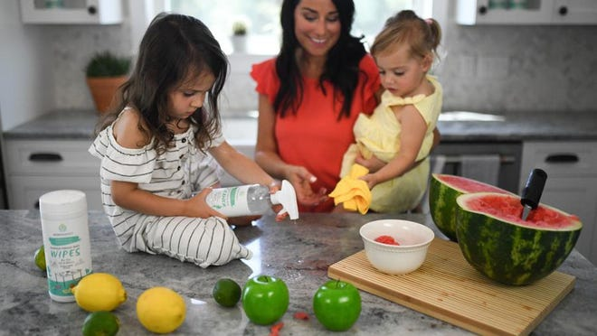 Jennifer Cosco, creator of MomRemedy, a household cleaner, watches her daughter Charlotte, left, apply the product to the counter while she holds her other daughter, Rose.