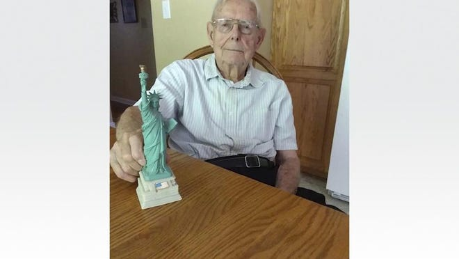 George North of Adrian, a World War II veteran who served in the U.S. Army, shows off a miniature figurine of the Statue of Liberty. The statue was a gift from North's doctor, Dr. Padmaja Mouli of Adrian. Each year, Mouli's office celebrates North's birthday. He turned 99 years old Oct. 17.