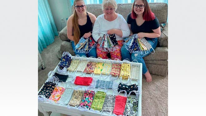 Shar Ann Packard, center, displays the many colorful face masks she has created at the beginning of the coronavirus pandemic. Packard has not created the face masks by herself. Assisting her have been her granddaughters Lexi, left, and Dana Holtz.
