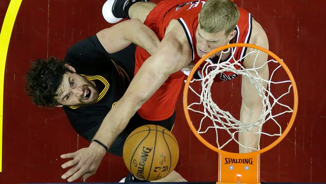 Cleveland Cavaliers forward Kevin Love (0) shoots against Portland Trail Blazers center Mason Plumlee, right, during the first half of an NBA basketball game Tuesday, Dec. 8, 2015, in Cleveland.