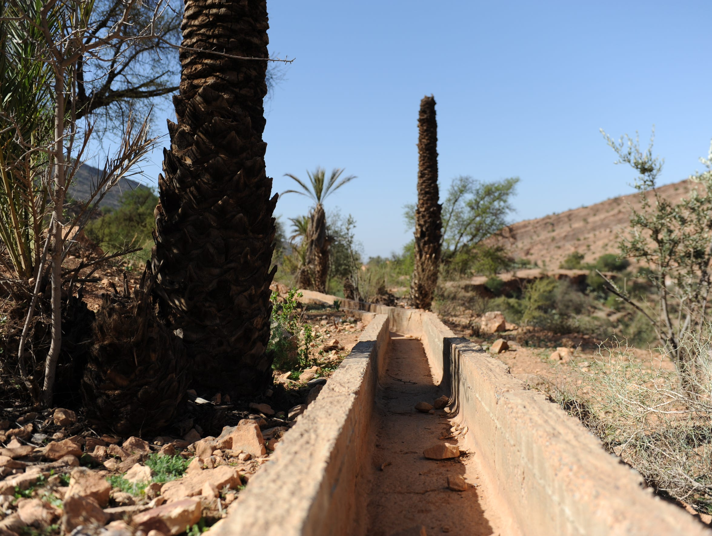 An old canal in the village of Assads is dry and strewn