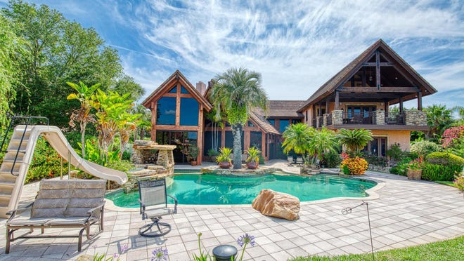 The spectacular pool area is a tropical oasis, with amazing rock work, a slide, spa and a gas fireplace. Just beyond, there is a pier that leads to the boathouse, dock and lift.