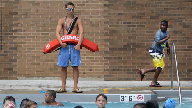 Lifeguard Jack McLaughlin watches over children at the Pleasant Ridge Recreation Center pool last year. City pools are short 65 lifeguards as the swim season is upon us.