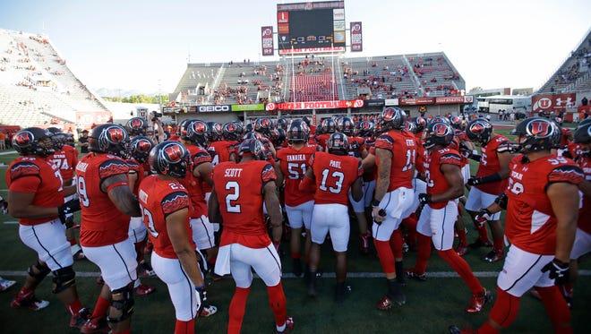 Members of the Utah football team huddle before the start of their NCAA college football game against Utah State Friday, Sept. 11, 2015.