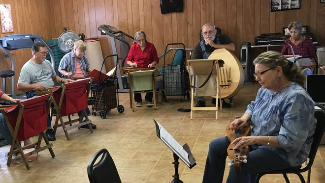 A group of dulcimer players practice at the JD Lewis Senior Center, which will not receive money from the County Commission next year, as  donations to all non-profit agencies have been cut to  help balance the county's budget.