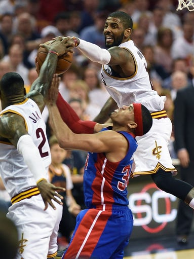 Cavs' LeBron James (left) and Kyrie Irving block a