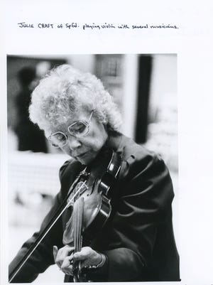 Julie Craft of Springfield playing violin with several musicians.