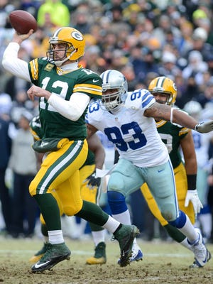 Green Bay Packers quarterback Aaron Rodgers (12) throws as Dallas Cowboys defensive end Anthony Spencer (93) closes the distance in the second quarter. The Green Bay Packers hosted the Dallas Cowboys in an NFC divisional playoff at Lambeau Field.