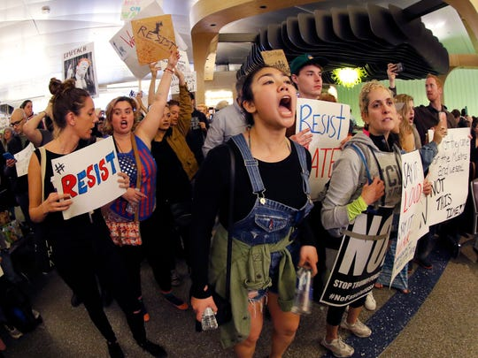 Demonstrators chant inside Tom Bradley International Terminal as protests against President Donald Trump's executive order banning travel from seven Muslim-majority countries continue at Los Angeles International Airport Sunday, Jan. 29, 2017.