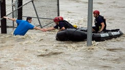 Rescue personnel grab the the hand of a man stranded