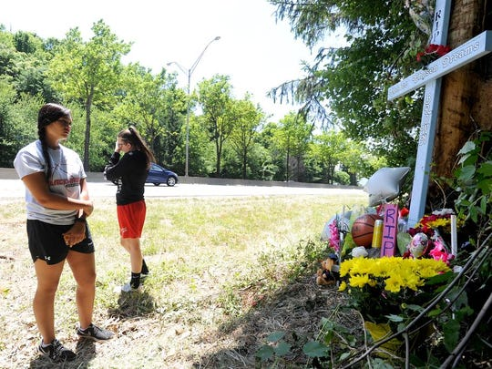 """Monica Taylor, 19, left, and Morgan Kisselburg, 20, stop by the roadside memorial on Monday to write a message to their friend Chance Brown, who died in a car wreck at the spot Sunday morning along Interstate 240 near the Charlotte Street exit. """"I don't know anyone that didn't like her and I don't know anyone that she didn't like,"""" Kisselburg said about her friend. """"I never saw her without a smile on her face. She was always in the best mood and that's just how I think everyone is trying to remember her."""""""