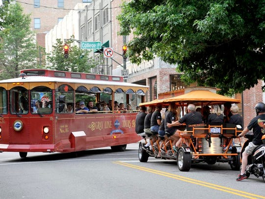 Asheville, North Carolina is a city known for bringing in tourists -- nearly 11 million a year. Here, one group rides the Amazing Pubcycle while another enjoys a guided tour on the Gray Line Trolley Tour of Asheville.