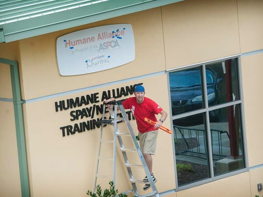 Matt Husky, with Signorama, replaces the sign on the Humane Alliance's spay and neuter clinic signifying the clinic's acquisition by the ASPCA.