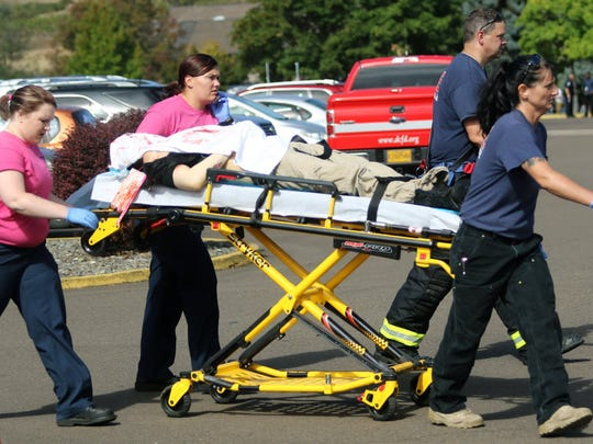 Authorities carry a shooting victim away after a gunman