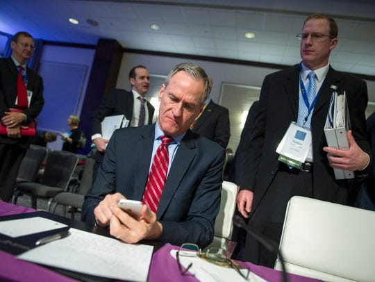South Dakota Gov. Dennis Daugaard checks his cell phone
