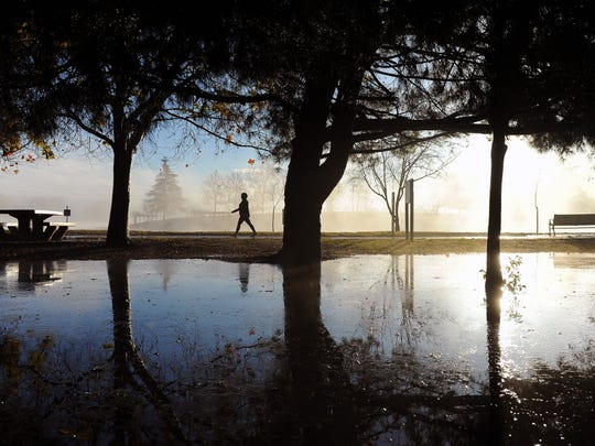 A person strolls past rain puddles at Lake Balboa Park