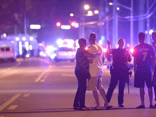 Police officers direct family members away from Pulse nightclub in Orlando, Fla., after 49 people died in a mass shooting.