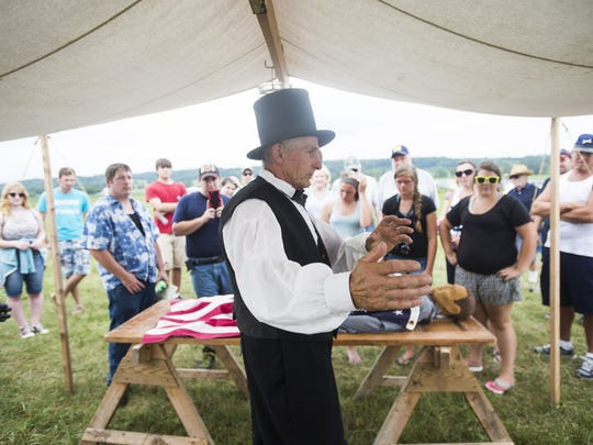 Re-enactor Ralph Aitkin of Lewistown explains to a crowd how an embalming surgeon worked during the Civil War at the 152nd Battle of Gettysburg re-enactment Aug. 7, 2015 in Gettysburg.