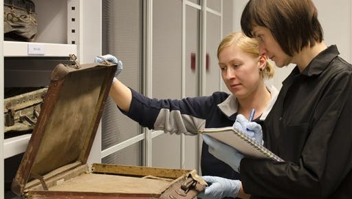In this undated photo provided by the Auschwitz-Birkenau State Museum employees inspect a victim's suitcase that is kept in the recently-opened, state-of-the-art protective storage at the Auschwitz Museum in Oswiecim, Poland. The Auschwitz museum says some of the victims' 3,800 suitcases have been put into a state-of-the-art protective storage room partly funded by the European Union.