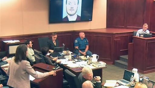 FILE - In this July 28, 2015, file image, made from Colorado Judicial Department video, defense attorney Tamara Brady, left, questions Robert Holmes, top right, the father of James Holmes, background left, during the sentencing phase of the Colorado theater shooting trial in Centennial, Colo. Jurors in the Colorado theater shooting trial reached a decision Monday, Aug. 3, 2015, on whether to keep the death penalty as an option for Holmes. The jury deliberated for less than three hours, starting Thursday after Holmes' parents made an emotional plea for their son's life because he is mentally ill. (Colorado Judicial Department via AP, Pool, File)