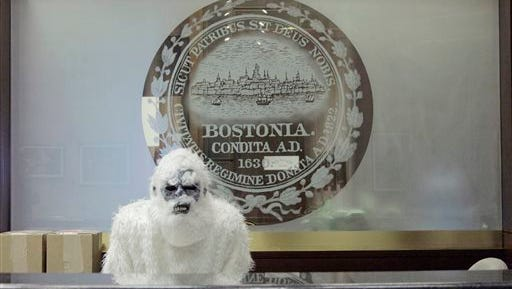 "FILE - In this March 6, 2015 file photo provided by Eric Gulliver, an anonymous creature known as The Boston Yeti poses in front of the Boston logo at City Hall in Boston. The Yeti, who provided much-needed comic relief during the city's record 9 feet of snow, will take the stage to field questions from the public at a Dec. 17, 2015, screening of ""Rudolph the Red-Nosed Reindeer,"" at Brattle Theater in Cambridge, Mass."
