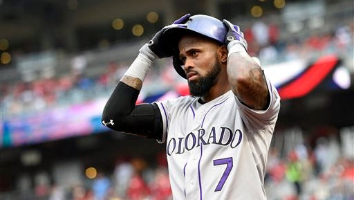 FILE - In this Aug. 7, 2015, file photo, Colorado Rockies shortstop Jose Reye  adjusts his batting helmet before a baseball game against the Washington Nationals in Washington. Reyes was placed on paid leave Tuesday, Feb. 23, 2016, under Major League Baseball's new domestic violence policy and will not report to spring training. The 32-year-old, a four-time All-Star, was arrested in Hawaii at a Maui resort on Oct. 31 following an argument with his wife and pleaded not guilty to a charge of abuse of a family or household member.  (AP Photo/Nick Wass, File)
