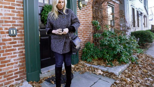 FILE - In this Dec. 12, 2014 file photo, Boston Marathon bombing survivor Heather Abbott walks out the door of her home in Newport, R.I. Rhode Island lawmakers are considering legislation to make victims of terrorist attacks eligible for compensation even if the attack happened outside the state. The bill is a response to the bureaucratic struggles encountered by Abbott when she applied for the state's crime victim compensation fund after the April 2013 attack. The House voted to pass the bill in March 2016. It faces a Senate committee hearing Tuesday, April 5, 2016 at the State House in Providence.