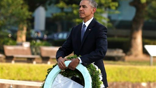 President Barack Obama carries wreaths Friday at Hiroshima Peace Memorial Park. He is the first sitting U.S. president to visit the site of the world's first atomic bomb attack.