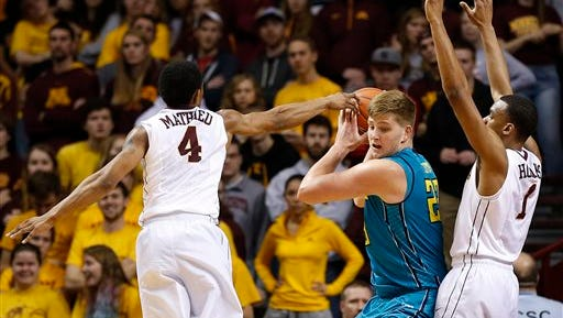 UNC Wilmington's C.J. Gettys (23) protects the ball in a 2014 NCAA Tournament game vs. Minnesota.