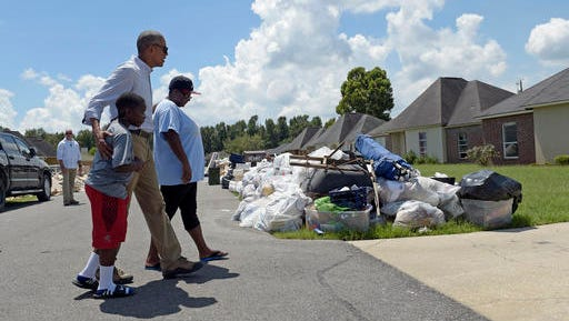 President Barack Obama walks with a family to tour their flood-damaged home in the Castle Place neighborhood of Baton Rouge, La., Tuesday, Aug. 23, 2016. Obama is making his first visit to flood-ravaged southern Louisiana as he attempts to assure the many thousands who have suffered damage to their homes, schools and businesses that his administration has made their recovery a priority. (AP Photo/Susan Walsh)