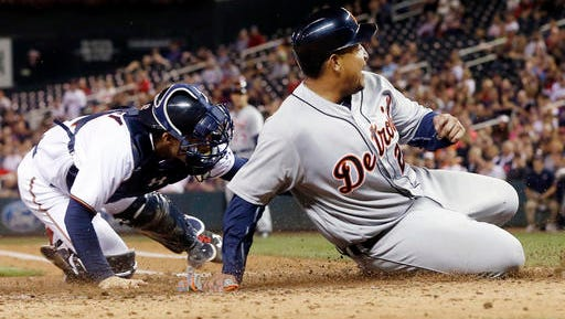 Detroit Tigers' Miguel Cabrera, right, beats the tag by Minnesota Twins catcher John Ryan Murphy in the fourth inning.