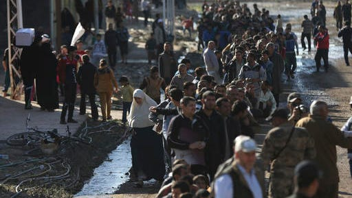Iraqi citizens stand in a long line to receive food supplies, at al-Arbajiyeh neighborhood, in Mosul, Iraq, Saturday, Nov. 19, 2016. Iraqi troops faced stiff resistance Saturday from Islamic State militants as they pushed deeper into eastern Mosul, backed by aerial support from the U.S.-led international coalition, a senior military commander said.