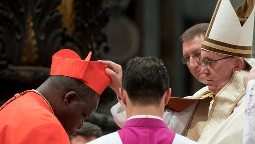 New Cardinal Dieudonne Nzapalainga, Archbishop of Bangui, Central African Republic, receives the red three-cornered biretta hat during a consistory inside the St. Peter's Basilica at the Vatican, Saturday, Nov. 19, 2016. In the ceremony to formally give the Catholic church 17 new cardinals, Francis lamented how immigrants, refugees, and those from different races or faiths are increasingly seen as enemies.