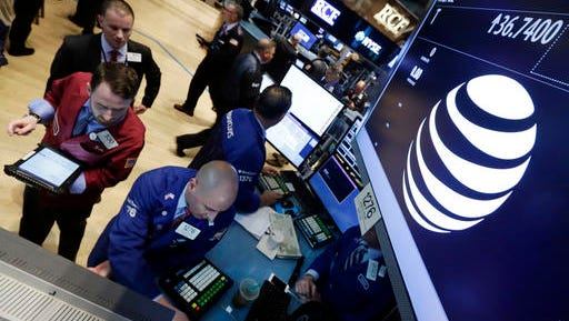 FILE - In this Monday, May 19, 2014, file photo, traders gather at the post that handles AT&T on the floor of the New York Stock Exchange. AT&T says the market for its new internet cable service, DirecTV Now, could be as large as 20 million households.
