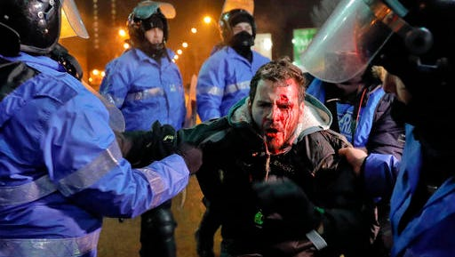 Romanian riot police detain a man, face covered in blood, after minor clashes erupted during a protest in Bucharest, Romania, Thursday, Feb. 2, 2017. Brief clashes broke out between protesters and police in Romania's capital, as tens of thousands of people protested for the second night a government decision to decriminalise official misconduct.