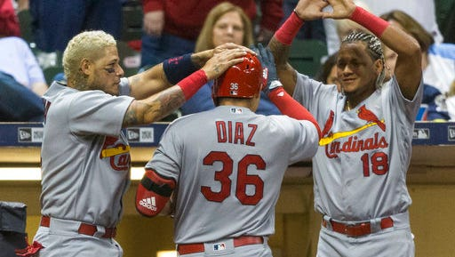 St. Louis Cardinals' Aledmys Diaz is greeted at the dugout by teammates Yadier Molina, left, and Yadier Molina after hitting a solo home run off of Milwaukee Brewers' Carlos Torres during the seventh inning of a baseball game Saturday, April 22, 2017, in Milwaukee.