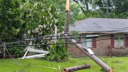 Trees and downed power lines sit in the yards of houses today  in Liberty. A strong storm line passed through southwest Mississippi, toppling trees and power lines, leading to power outages and traffic disruptions, as well as causing minor property damage throughout the area.