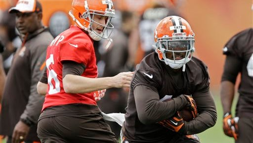 Cleveland Browns running back Ben Tate, right, takes a handoff from quarterback Brian Hoyer (6) during a voluntary minicamp workout at the NFL football team's facility in Berea, Ohio, Thursday, May 1, 2014. (AP Photo/Mark Duncan)