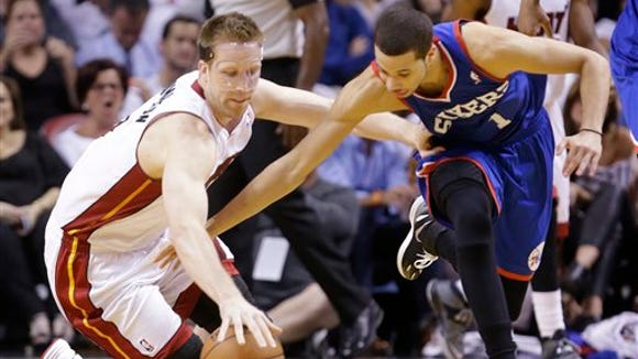 Sixers point guard Michael Carter-Williams, right, and Miami Heat center Justin Hamilton battle for a loose ball during the second half of Philadelphia's 100-87 victory both teams' regular-season finale Wednesday in Miami.