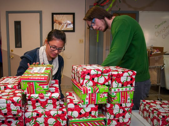 Volunteers Elizabeth Choo and Kenton Baker package donated shoe boxes full of school supplies, candy and personal items at the First Evangelical Free Church on Wednesday as part of Operation Christmas Child.