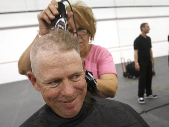 Stoney Brooks, of Farmington, gets his head shaved by Paula Cool during the Get Pinked rally on Oct. 3, 2014, at McGee Park in  Farmington.