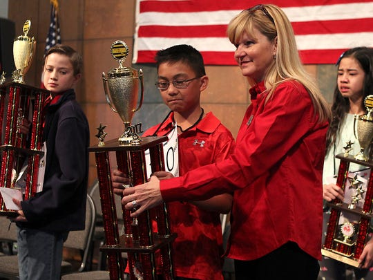 Kasey Torres, winner of the 29th annual San Angelo Spelling Bee, is awarded his first place trophy by emcee Debbie Valesquez, from Howard College. Davis Bailey (left) won 3rd place and Franchesca Untalan got 2nd place.