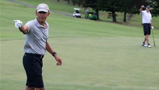 President Barack Obama celebrates after hitting a long chip shot on the 18th hole during a round of golf at Mid-Pacific Country Club, Monday, Dec. 21, 2015, in Kailua, Hawaii.