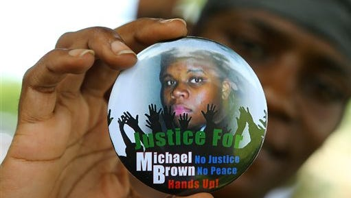 In this Aug. 21, 2014 file photo, Nikki Jones, of Spanish Lake, Mo, holds a button in support of Michael Brown while visiting the community in the apartment development near where he was fatally shot in Ferguson, Mo. After Brown's Aug. 9 shooting death at the hands of a white police officer his legacy continues to evolve.