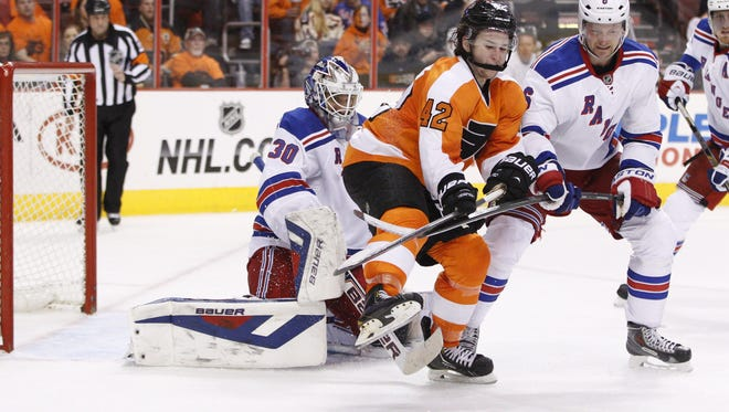 The Flyers' Jason Akeson, center, goes after the puck while being flanked by Rangers goalie Henrik Lundqvist, left, and Anton Stralman during the second period of Game 3  Tuesday night. The Rangers won 4-1 but need to stop taking dumb penalties and stay out of the penalty box.
