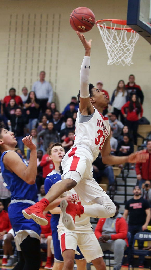 Hamilton's Daniel Barrera (32) goes up for a shot in front of Millbrook's Humberto Cabrera (3) during the boys Class C state regional semifinal at Beacon High School March 6, 2018. Hamilton won the game 65-58.
