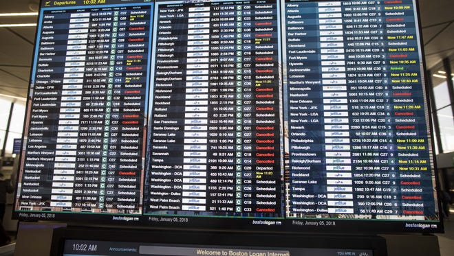 This file photo from Jan. 5, 2018, shows many delays and cancellations on a flight display board at Boston's Logan International Airport amid an earlier snow storm.