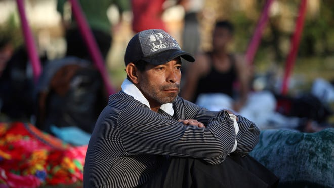 "A man sits amidst other sleeping migrants at a sports club where Central American migrants traveling with the annual ""Stations of the Cross"" caravan are camped out, in Matias Romero, Oaxaca State, Mexico, on April 3, 2018. The caravan of Central American migrants that angered U.S. President Donald Trump was sidelined at a sports field in southern Mexico with no means of reaching the border even as Trump tweeted another threat to Mexico Tuesday."