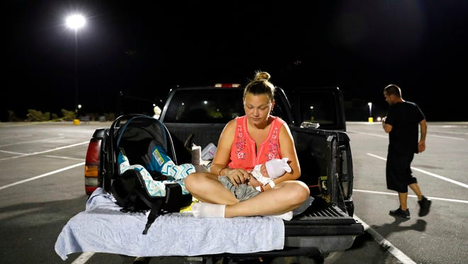 """Lorrainda Smith sits with her 2-day-old son, Luke, as she contemplates with her husband, Wilmer Capps, right, sleeping in their truck in a parking lot after their home was damaged from Hurricane Michael and they were told a nearby shelter was closed, in Panama City, Fla., Oct. 15, 2018. """"One day we had it all, the next we had nothing,"""" said Smith. """"This is not what I thought I'd be bringing him back to."""" The family eventually received a police escort to a nearby hospital for assistance as a nightly curfew prohibits the public from being out past dark."""